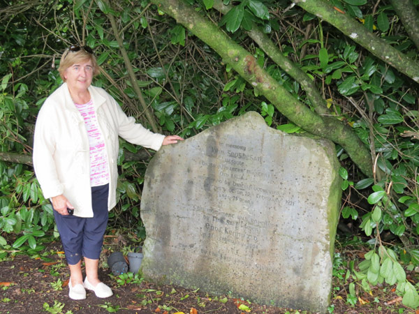 The author's cousin Marion O'Connor stands beside the memorial to John Geoghegan where he was shot by the Black and Tans