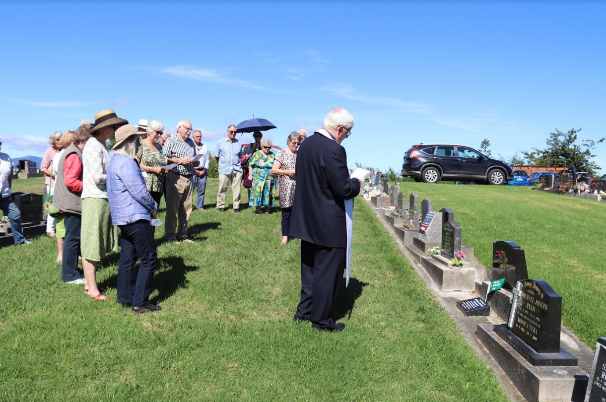 A large group watch on as Fr Eamon blesses the headstone and grave of Paddy Sullivan at the Otaki cemetery